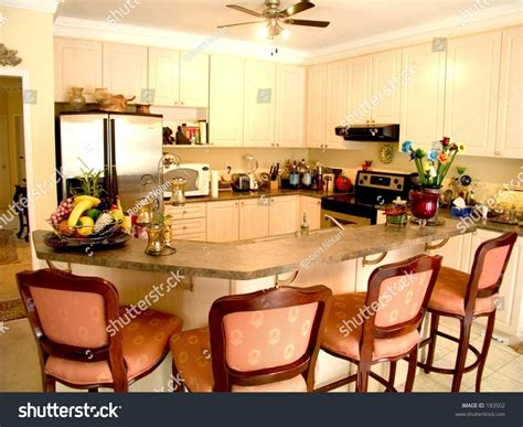 kitchen island table with 4 chairs modern kitchen with island table four chairs fridge stove and ceiling fan stock photo 183502