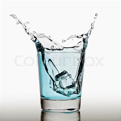cool glass cube splashing in a cool glass of water stock photo