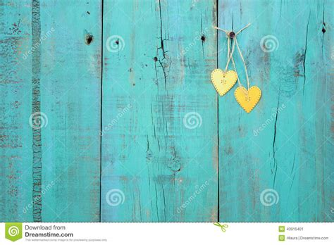 Cottage Home Plans two gold hearts hanging on antique teal blue wood fence