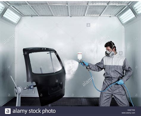 spray painting sop worker spray painting the door of a car boot paint shop