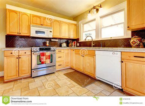 Kitchen Designs Unlimited light tones wood kitchen with brick backsplash design