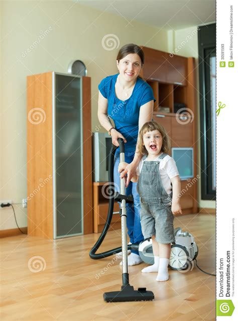 Parent Teaches Daughter Child Cleaning Room Stock